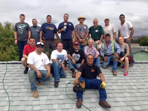 Equipe que ajudou idoso em reforma posa reunida em cima do telhado, após o conserto